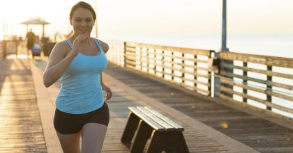 Overweight woman on pier in morning, running toward camera.